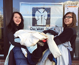 Two volunteers holding up an armful of coats for donation - One Warm Coat