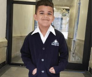 boy smiling wearing school uniform with pride