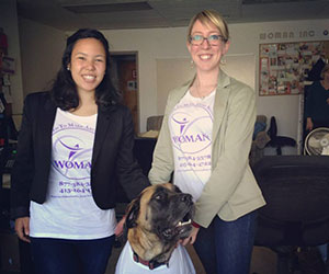 Two women with their dog wearing the organization tshirt - - WOMAN