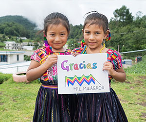 Little girls holding up a Thank You note - Mil Milagros