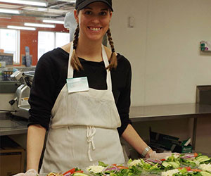 Volunteer preparing packed salad lunches - People Making a Difference