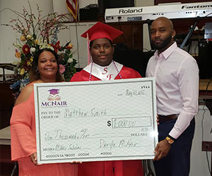 A graduate receiving a check - McNair Foundation
