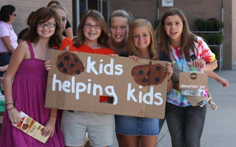 Kids holding a sign that says kids helping kids