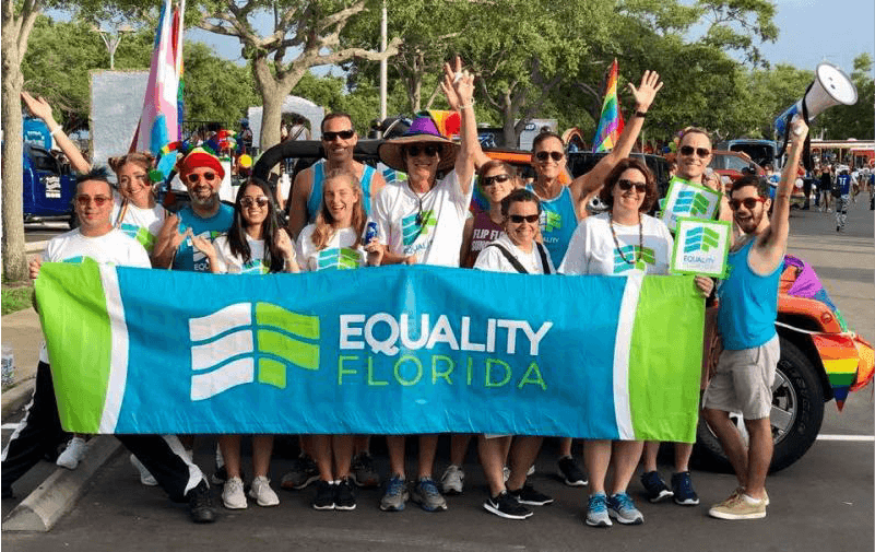 People with rainbow flags holding a sign that reads Equality Florida