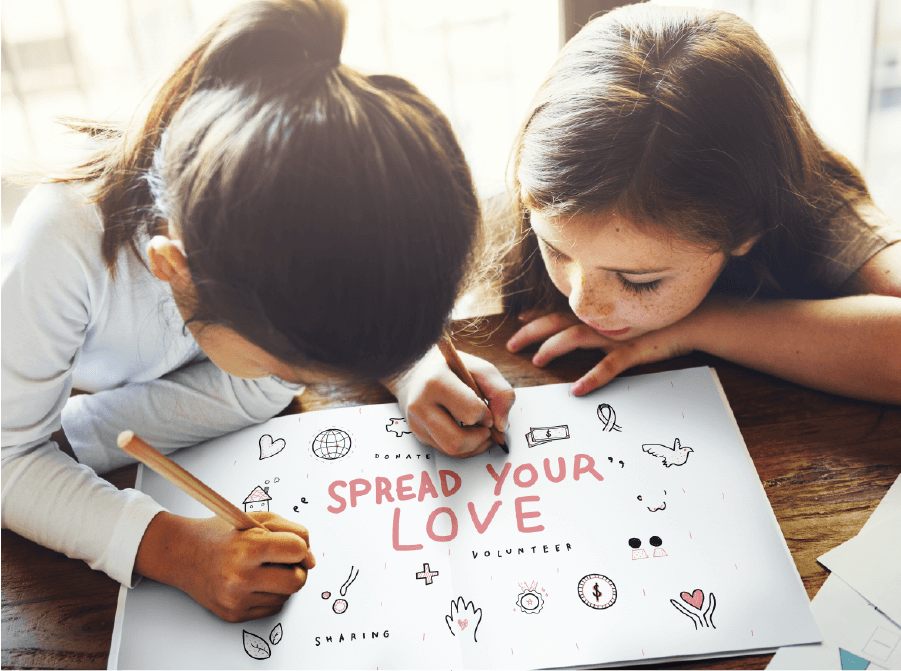 two cute girls drawing on a notebook that reads Spread Your Love