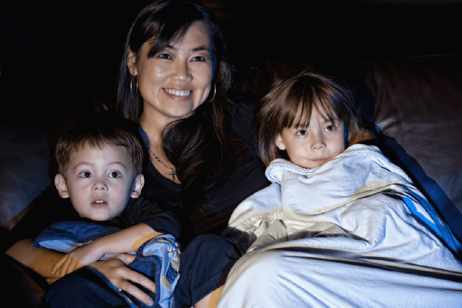 woman watching a movie with her 2 children on the couch