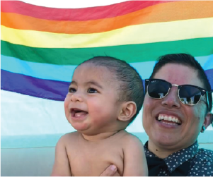 Woman holding young child in front of Pride flag