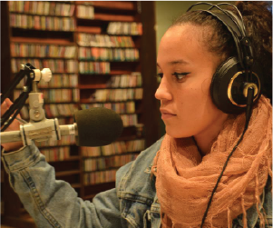 young woman at radio studio in front of microphone