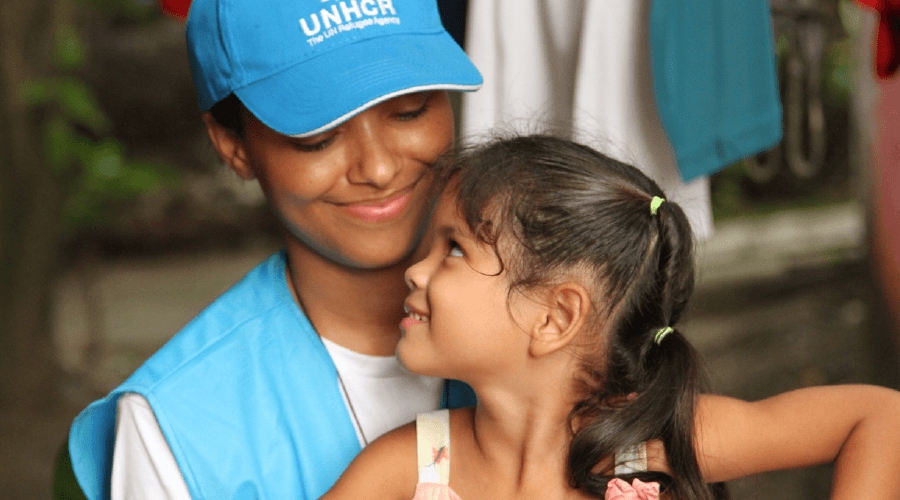 UNHCR volunteer hugging young girl