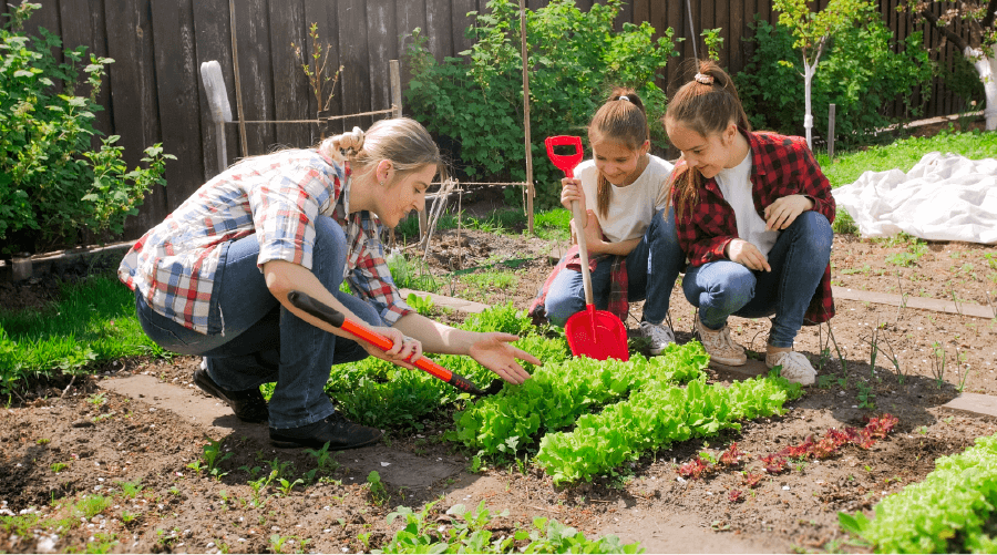 woman showing two young girls how to garden