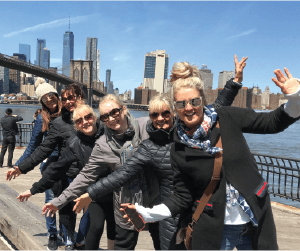 Group of people with open arms with Brooklyn Bridge in the background