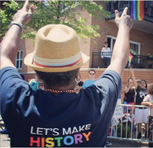 person wearing LGBTQ shirt that reads Let's make history