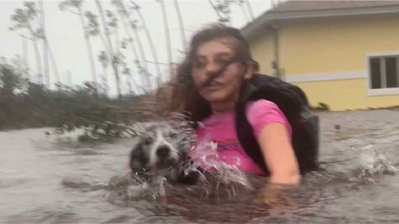 Girl carrying her pet dog as she is being rescued from her flooded home during Hurricane Dorian