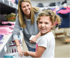 Little girl happily choosing some clothes - Ohio Newsboys Association