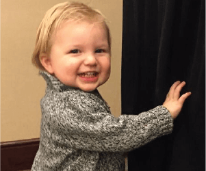 Toddler playing with the curtain - Heartbeat International