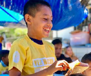 boy eating sandwich looking happy