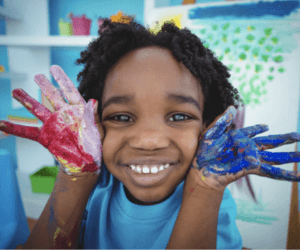 boy smiling showing his hands covereded in red and blue paint