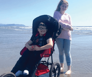 little boy with his new wheelchair at the beach Wheel To Walk Foundation