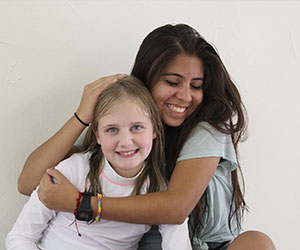 Volunteer hugging a little girl Arizona Lions Camp Tatiyee Inc
