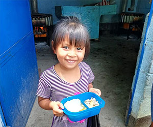 happy little girl holding her lunch Hunger Relief International