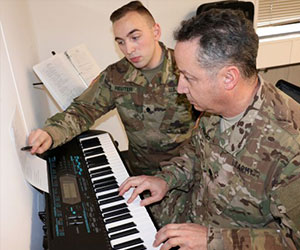 soldier teaching fellow soldier how to play the piano Starfish Foundation-Inc