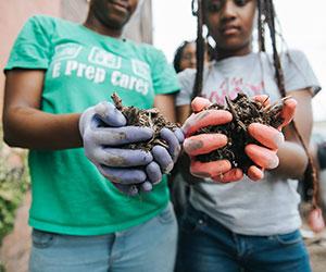 kid volunteers doing some planting Open Doors Academy
