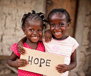 two kids holding up a hope sign A Childs Hope International, Inc.