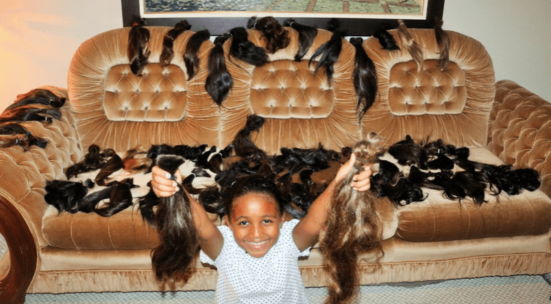 A young girl holds donated hair.