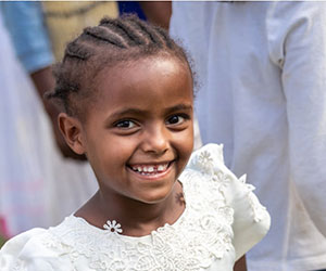 Smiling little girl in a white dress International Crisis Aid Inc