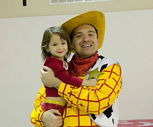 Volunteer dressed up as Woody holding a little girl Wichitas Littlest Heroes