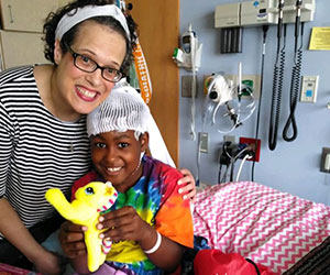 Volunteer visiting a sick boy Joyful Smiles Thru Faith