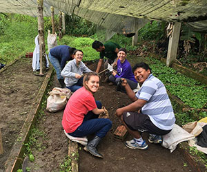Volunteers holding up produce CARMEN PAMPA FUND