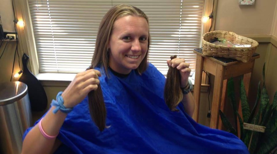 A girl sits in a hair stylist's chair after having her hair cut.