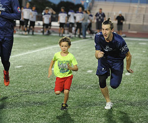 little kid running with his idol HopeKids