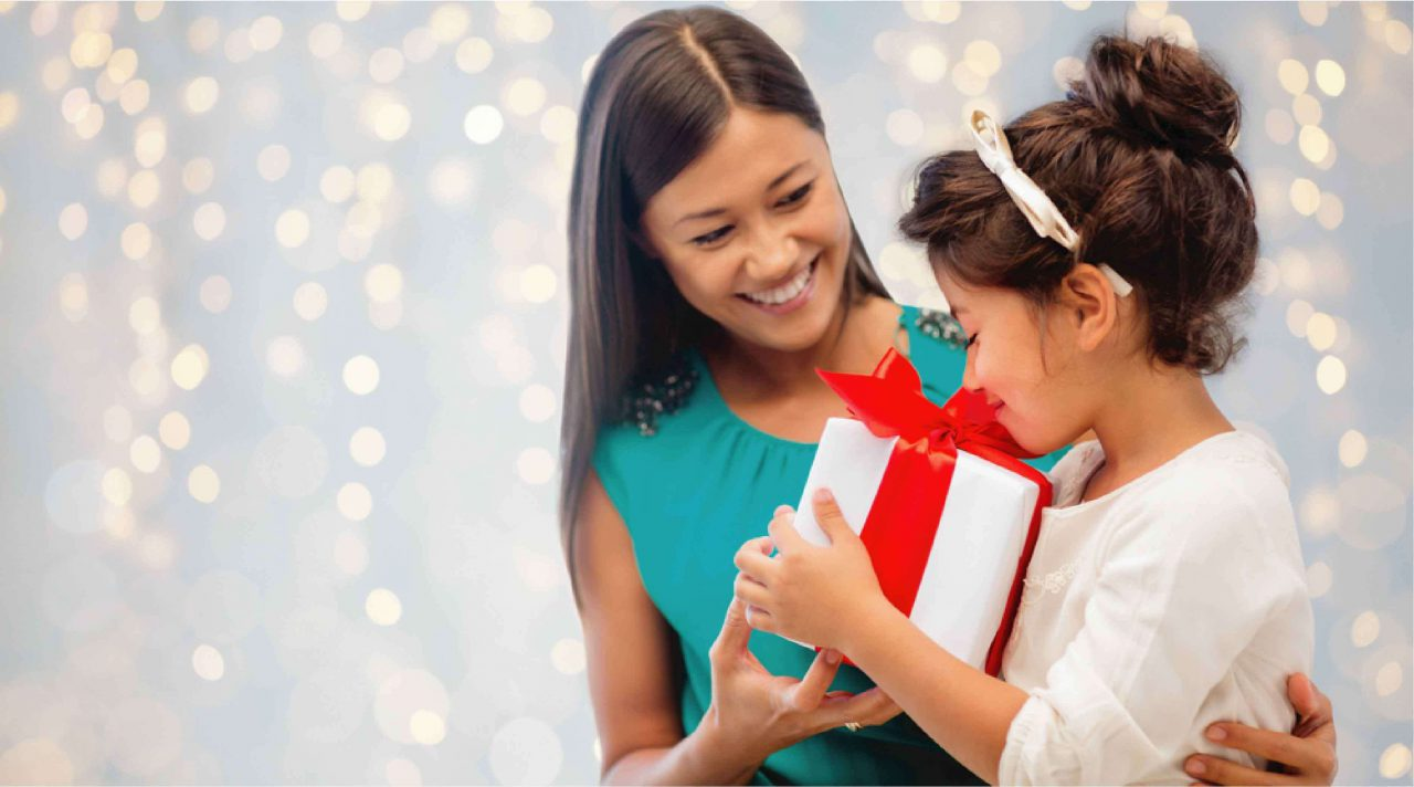 woman donating a gift to a girl during the holidays