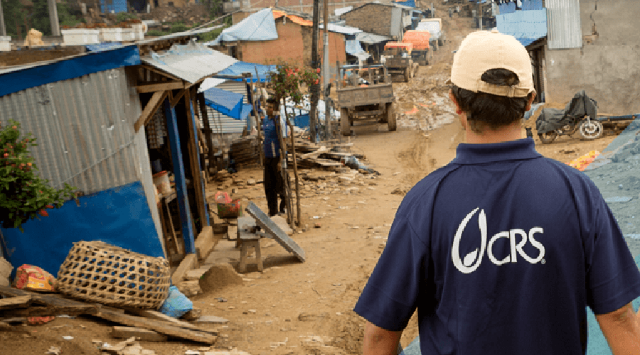 Man wearing Catholic Relief Services shirt facing disaster hit area